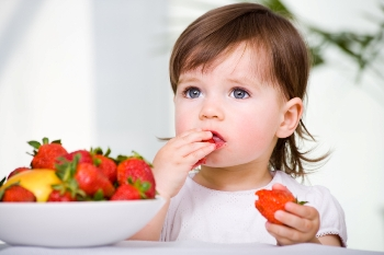 picture of a little girl eating strawberries